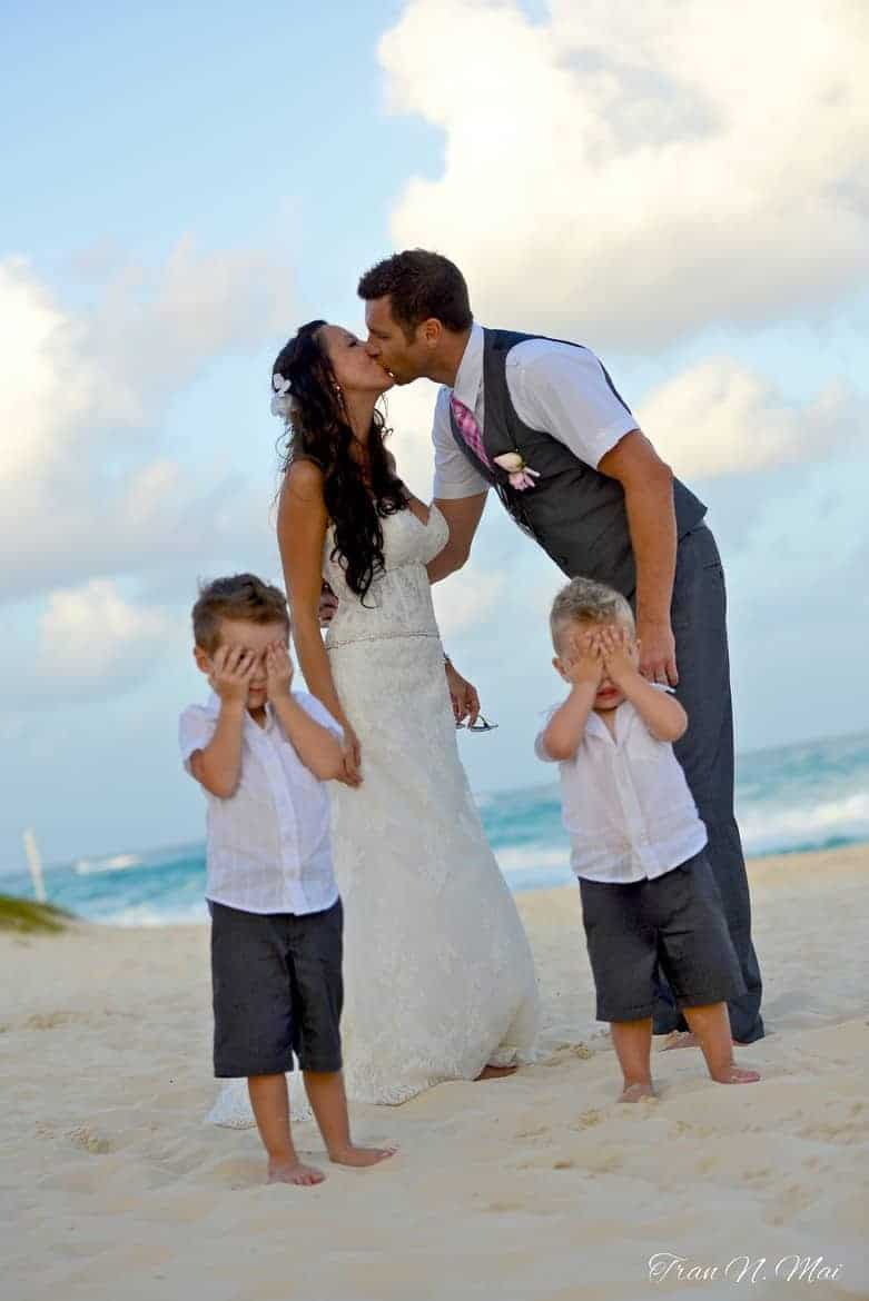 wedding kiss with kids covering eyes