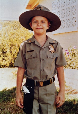 Christopher, age 7, smiling in his official police uniform.