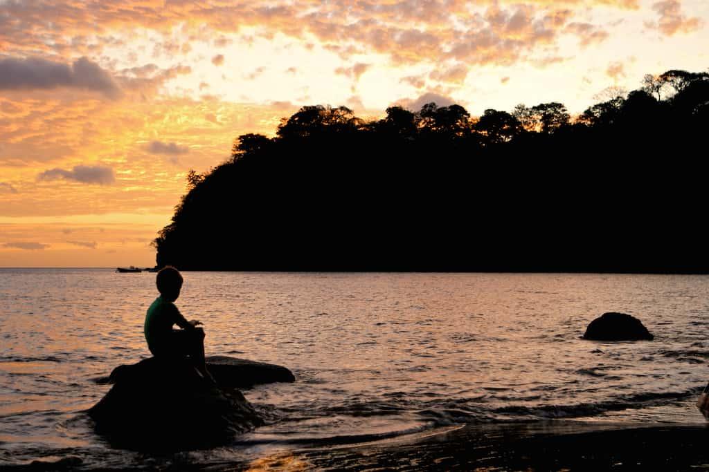 silhouette of boy on rocks on beach in costa rica