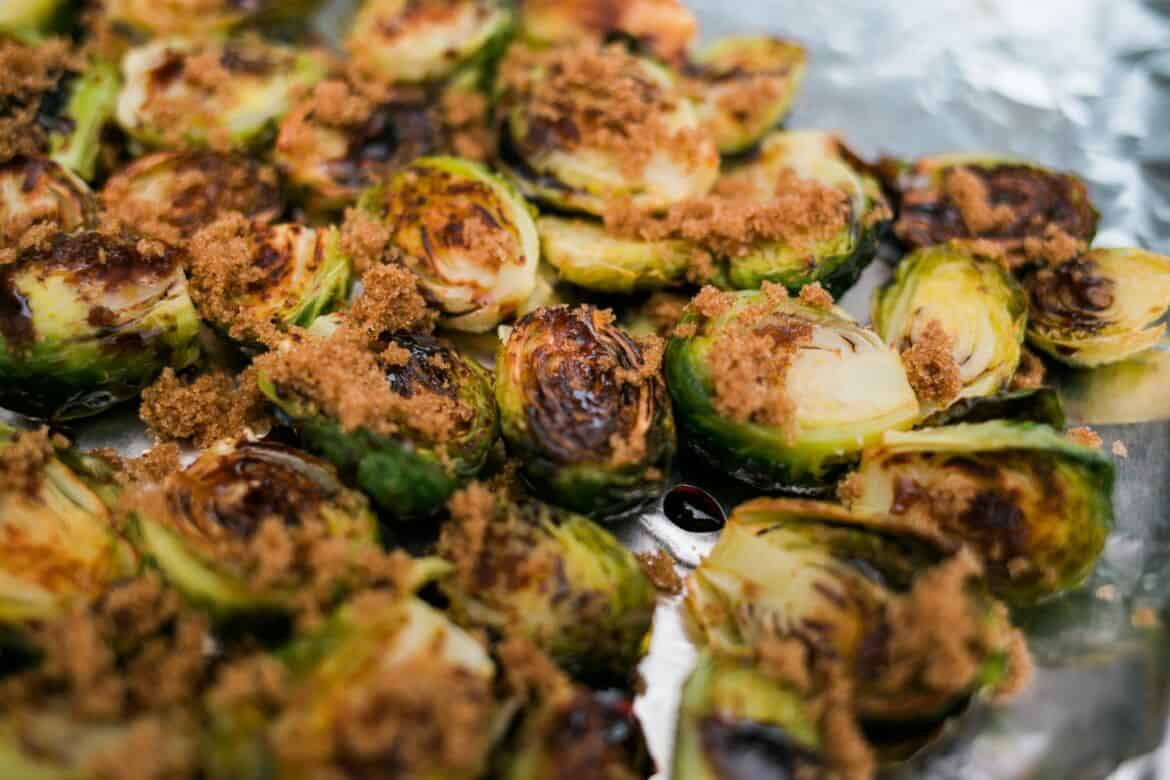brown sugar sprinkled on top of oven baked Balsamic Glazed Brussels Sprouts Recipe