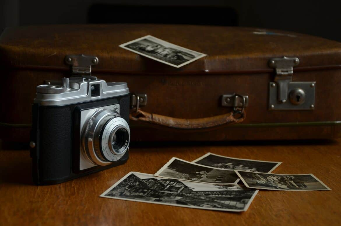 a film camera, photo prints and luggage as a reminder to take photographs for 30 Easy Pro Travel Tips You Should Be Following