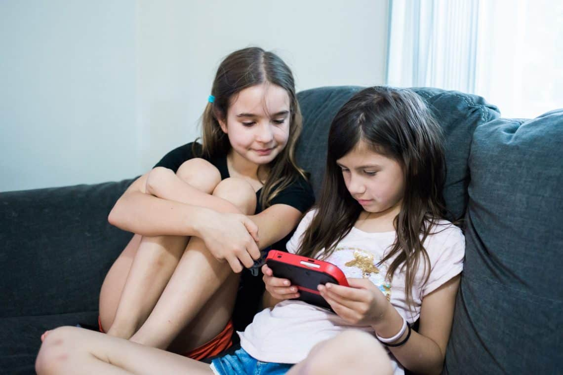 Family Game Night two young girls playing a Nintendo handheld game system