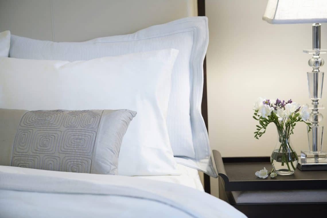 hotel bed and nightstand 1140x760 - How to Tell if Your Hotel Room is Actually Clean