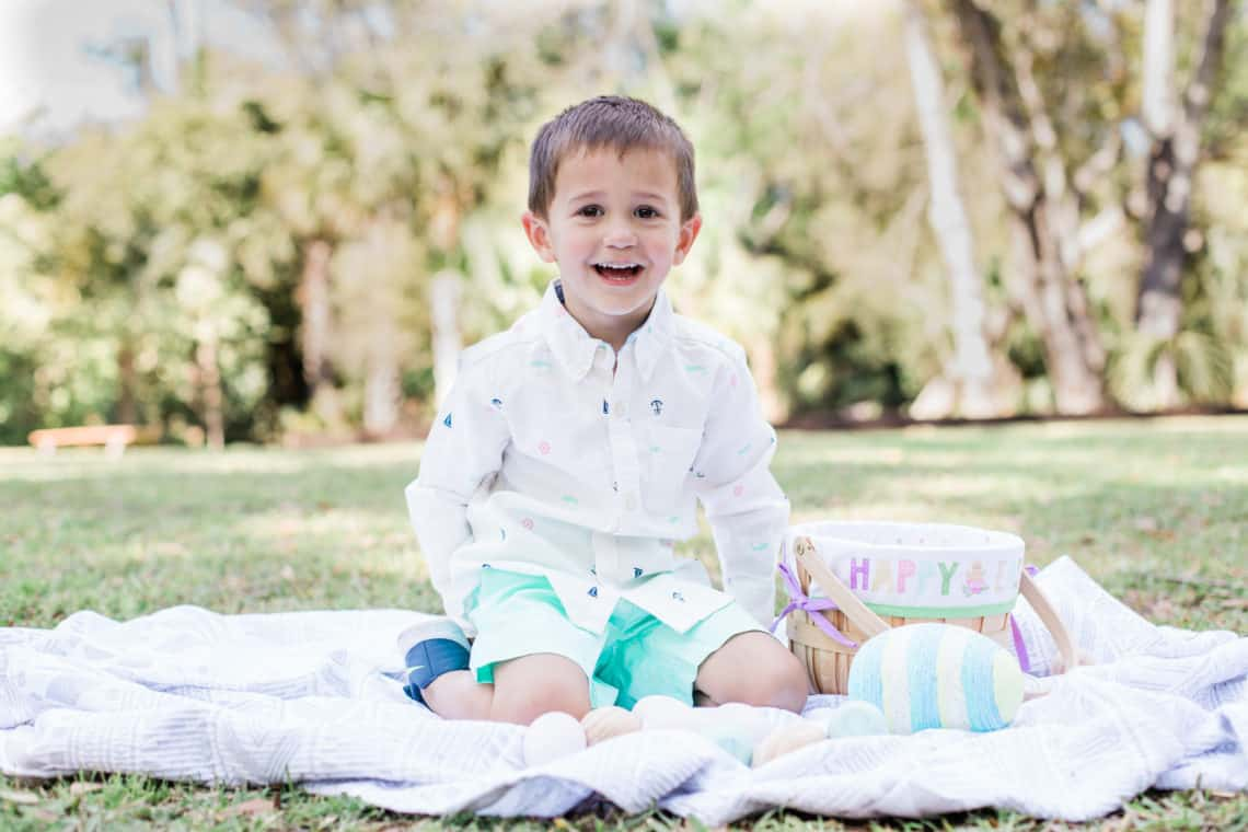 Toddler boy sits on a blanket with his easter basket wearing kids easter outfits