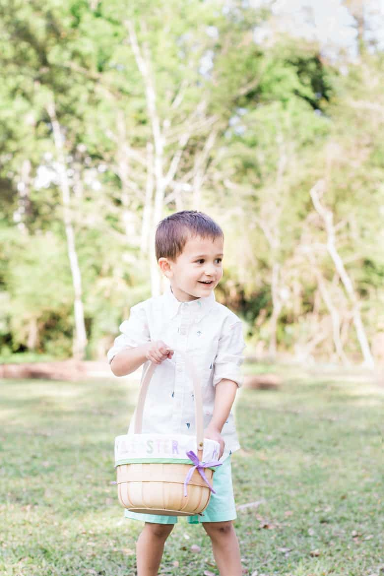 Toddler boy walks on the lawn carrying an easter basket wearing kids easter outfit