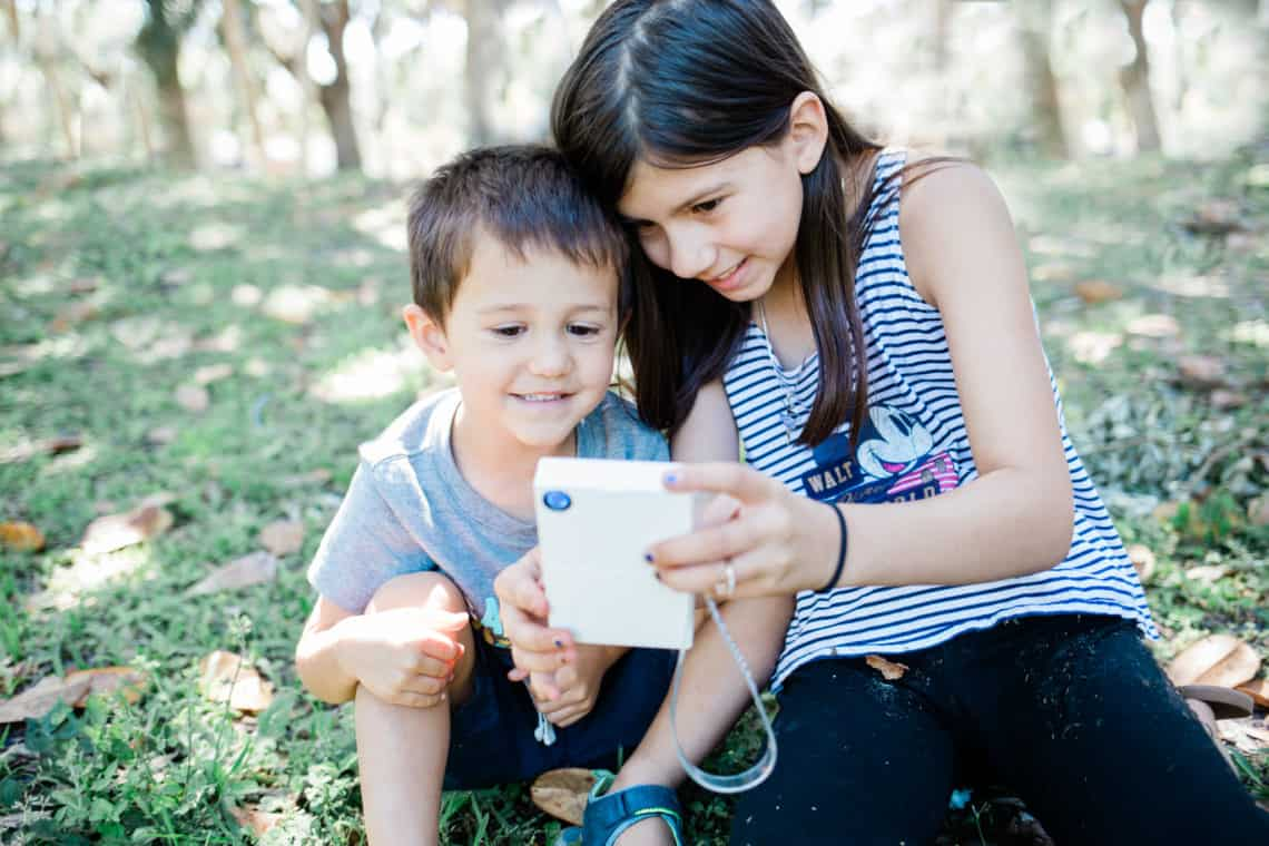 two young kids taking a selfie with the Polaroid Mint Camera in an article featuring for the creative way my kid is surviving deployment