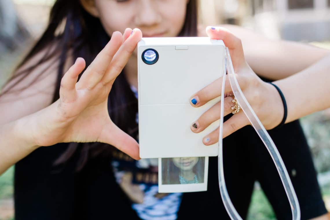 A polaroid camera printing a selfie of a young girl