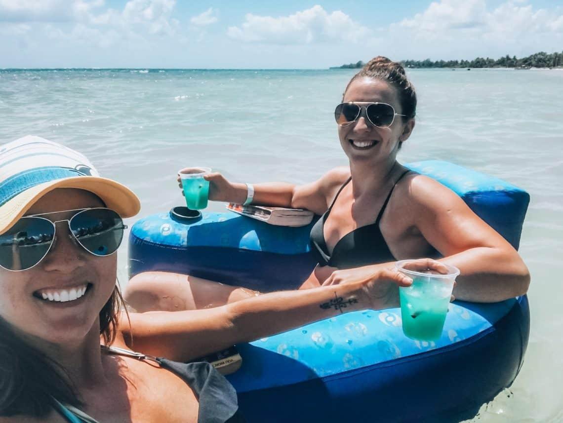 girls floating in ocean with drinks 2