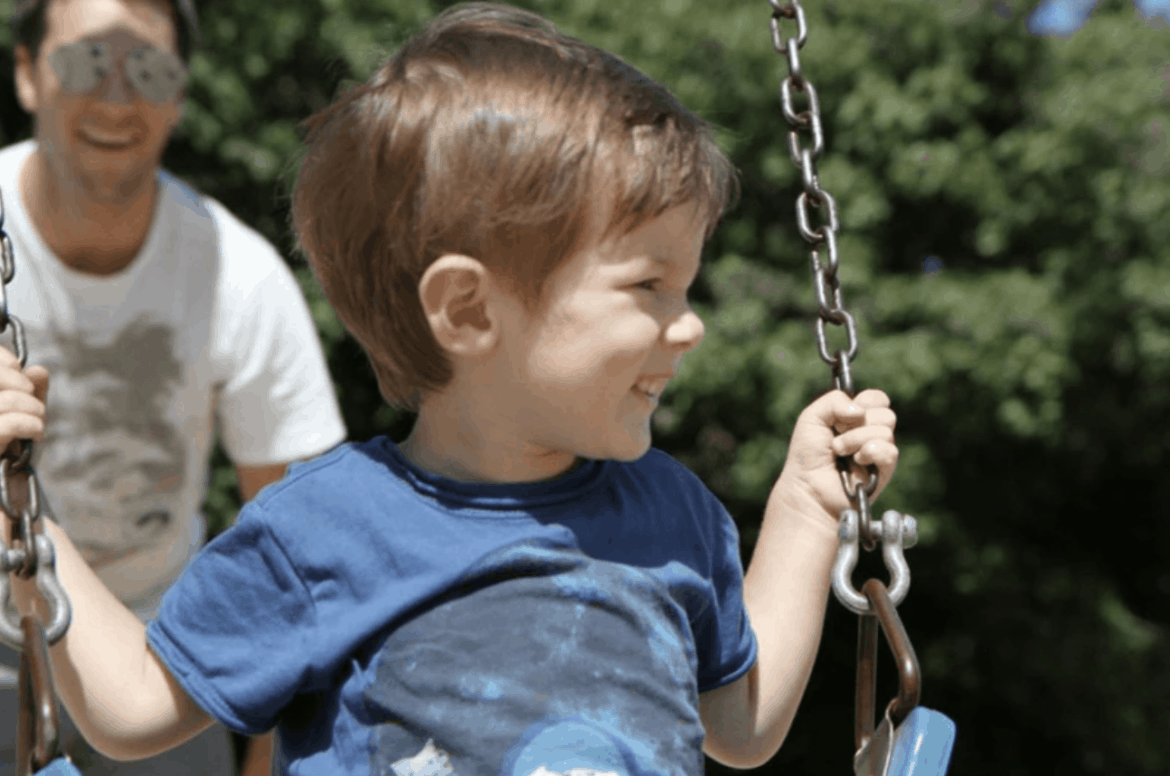 father pushing young boy on swing