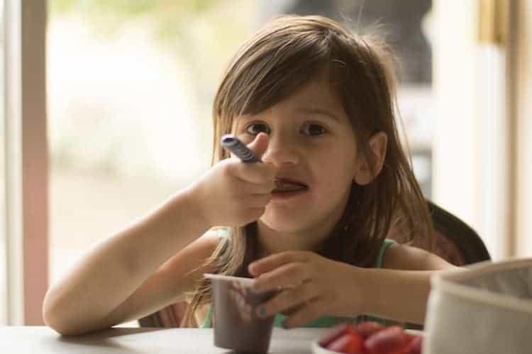 girl eating chocolate pudding