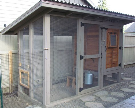 A wooden, fenced in chicken coop with steel roof Free DIY Chicken Coop Plans