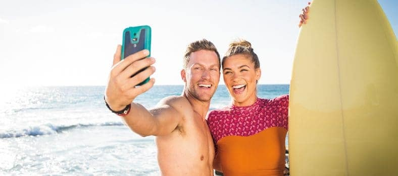 Male and female couple with a surf board taking a selfie next to the ocean
